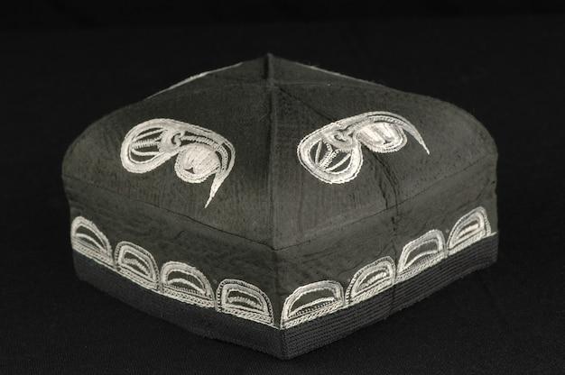 暗い背景に黒と白の頭蓋骨の伝統的なアジアの帽子