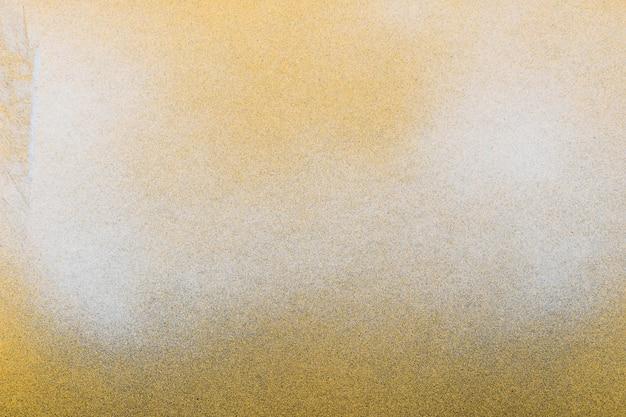 黄色の紙の背景に黒と白のスプレーペイント