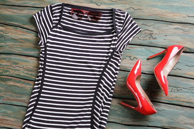 黒と白のストライプのトップ。サングラスと赤い光沢のあるかかと。緑の棚に女性の服。衣料品オークションの新商品。