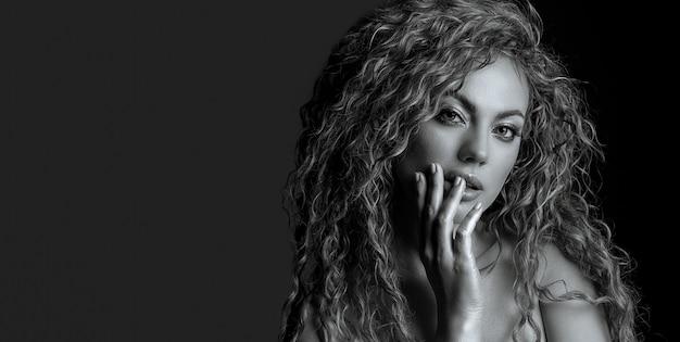 緑豊かな髪と裸の肩を持つ軽薄な女性の黒と白のスタジオポートレート。コピースペース