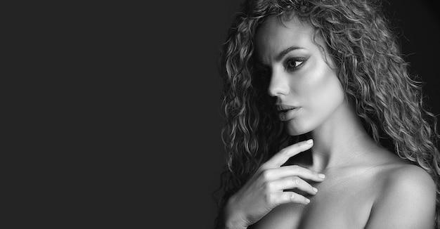 巻き毛と輝く健康な肌を持つ美しいブロンドの女性の白黒スタジオショット。テキスト用の空のスペース