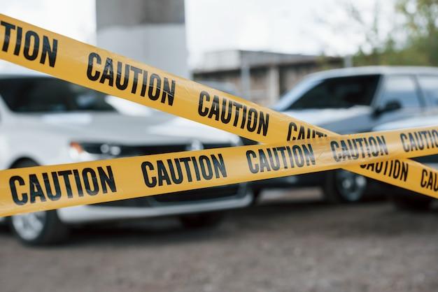 黒と白の車両。昼間の駐車場近くの黄色い注意テープ。犯罪現場