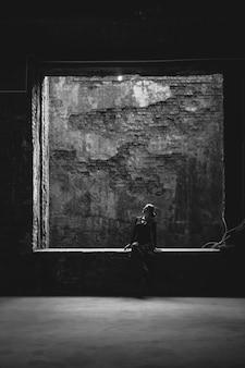 古い汚れた建物の大きな窓に座っている孤独な女性の黒と白のビュー