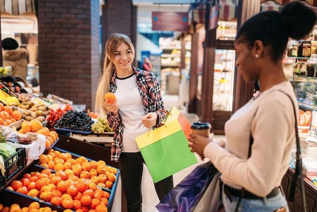 Черно-белые женщины покупают фрукты после покупок.