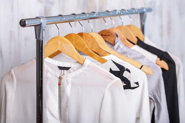 패션 스토어에서 선반에 나무 옷걸이에 흑인과 백인 여자 옷. 옷장 비즈니스 우먼