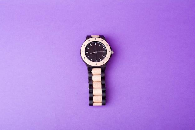 紫色の背景に黒と白の腕時計