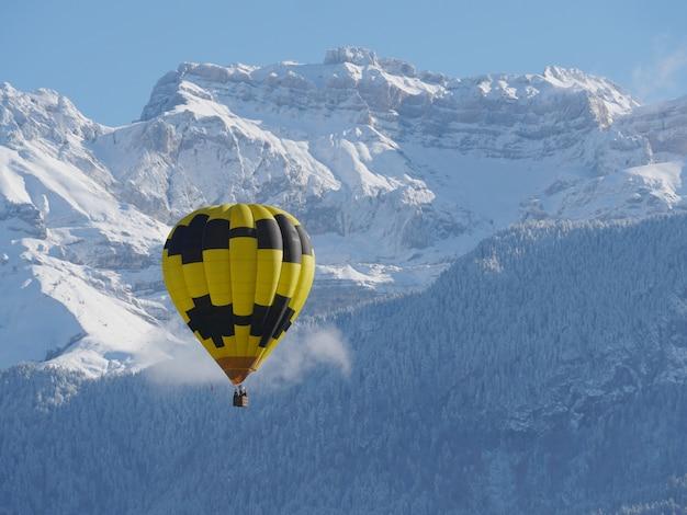 後ろに雪の山と黒と黄色の風船