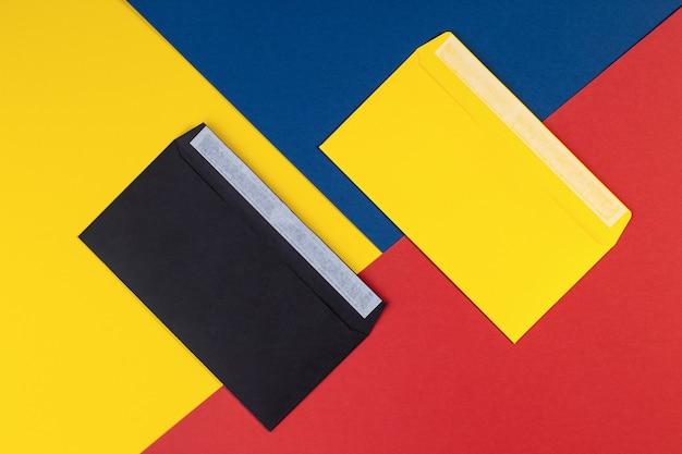 色とりどりの紙の背景に黒と黄色の封筒。ジオメトリの背景の最小限の概念。封筒付きの色とりどりの紙。コピースペースのあるクリエイティブなフラットレイアウト。上面図