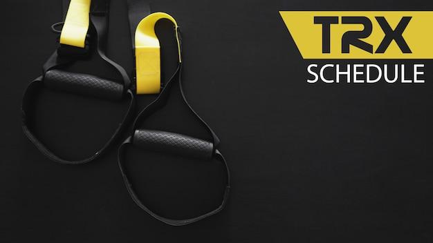 灰色の背景に黒と黄色のストラップ機能トレーニング機器。スポーツアクセサリー。フィットネスとジムのトレーニングアイテム。バナーtrxスケジュール