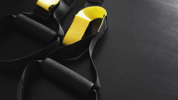 灰色の背景に黒と黄色のストラップ機能トレーニング機器。スポーツアクセサリー。健康のためのフィットネスとジムのトレーニングアイテム。バナーtrx