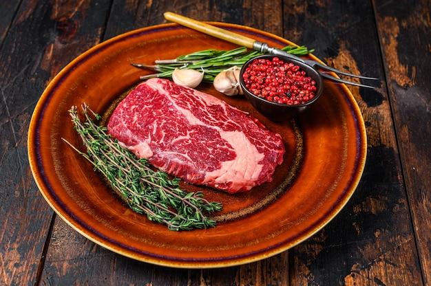 소박한 접시에 블랙 거스 립 아이 생 쇠고기 스테이크. 어두운 나무 배경입니다. 평면도.