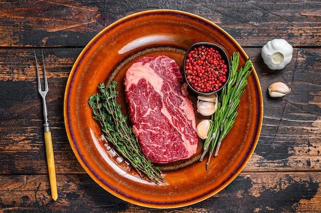 나무 테이블에 소박한 접시에 검은 앵거스 갈비뼈 원시 쇠고기 스테이크. 평면도.