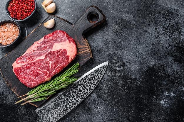 블랙 앵거스 리브아이, 칼로 나무 판자에 있는 생 립아이 쇠고기 스테이크. 검은 배경. 평면도. 공간을 복사합니다.