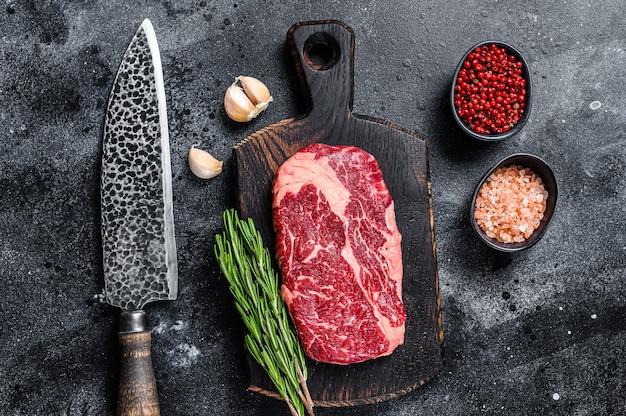 블랙 앵거스 ribeye, 블랙 테이블에 칼으로 나무 보드에 원시 갈비뼈 쇠고기 스테이크. 평면도.