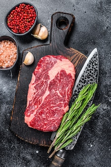 ブラックアンガスリブアイ、ナイフで木の板に生のリブアイビーフステーキ。
