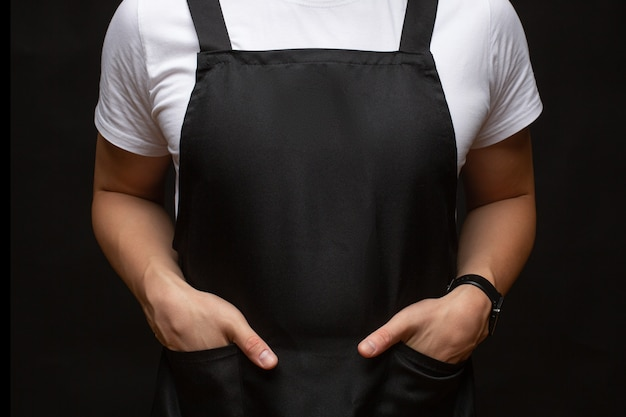 Black apron on a man closeup. hands in pockets. place for text. copy-space.
