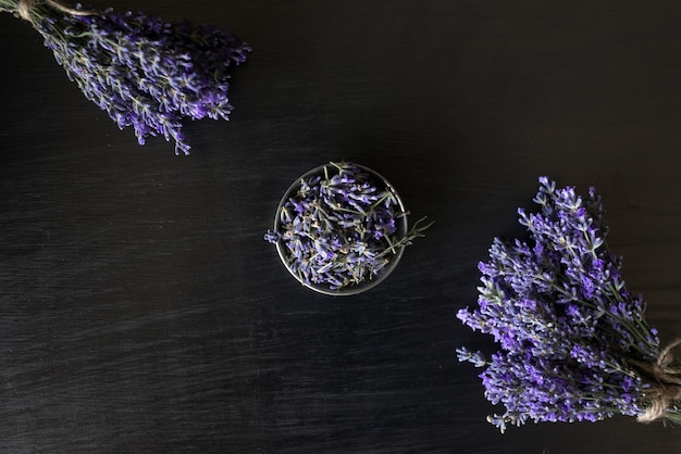 On black are bouquets of lavender scent and a bowl of fragrant flowers. flat lay