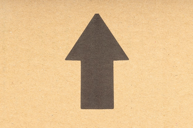 Черная стрелка вверх на коричневом картонном фоне. закрыть вверх