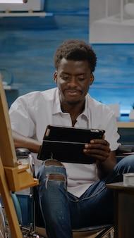 흑인 예술가는 디지털 태블릿을 사용하여 휠체어에 앉아 미술 그림에 대한 영감을 찾고 있습니다. 걸작을 디자인하는 예술 도구와 함께 아프리카계 미국인 민족의 젊은 잘못된 남자