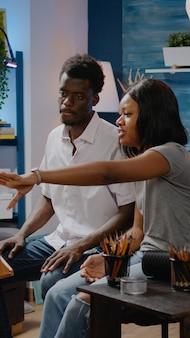 워크샵 스튜디오에서 드로잉 기술에 대해 이야기하는 흑인 예술 커플. 꽃병 디자인을 위한 성공적인 혁신적인 걸작을 작업하는 아프리카계 미국인 여성과 남성