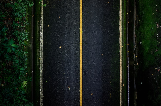 Black asphalt road that looks from top view with straight lines
