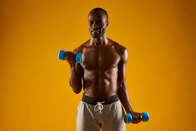 Black athletic man pumping up muscles by dumbbells in shade.