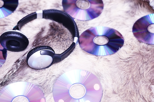 Черные аудионаушники на стопке глянцевых компакт-дисков с цветными бликами