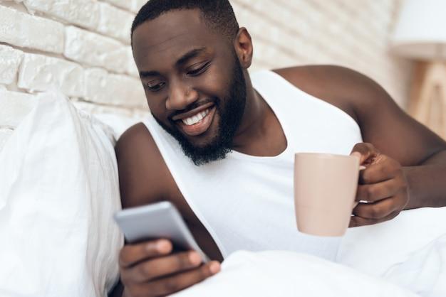 目覚めた黒人男性がベッドブラウジングでコーヒーを飲みます。