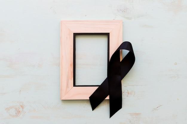 Black awareness ribbon on wooden empty frame over the wooden background