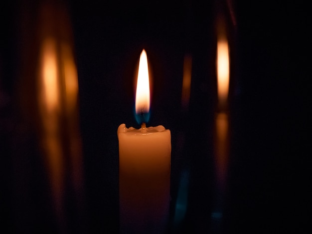 On a black background bright yellow candles, a holiday or a church burn