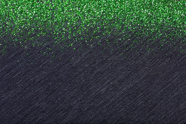Black background for christmas greeting card with green lights sequins.