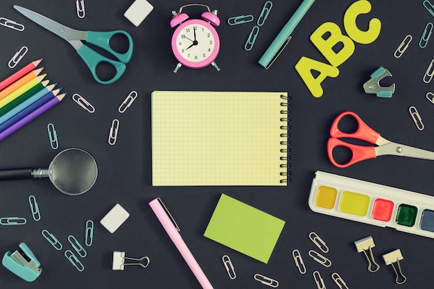 On a black background, color pencils, watercolor colors, magnifying glass and scissors are arranged in a circle