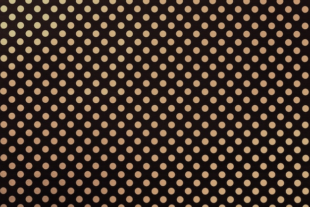 Black background from wrapping paper with a pattern of golden polka dot closeup.