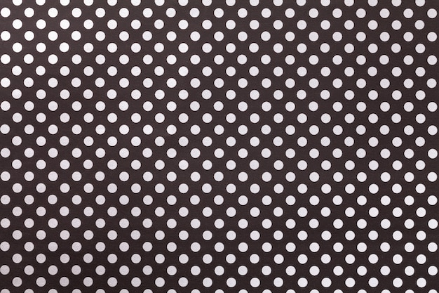 Black background from wrapping paper with a pattern of white polka dot closeup.