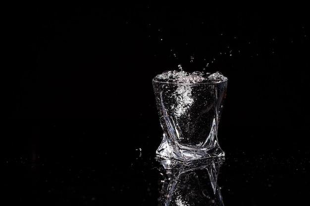 Черный фон - стакан, в который падает капля воды. брызги воды на стекло