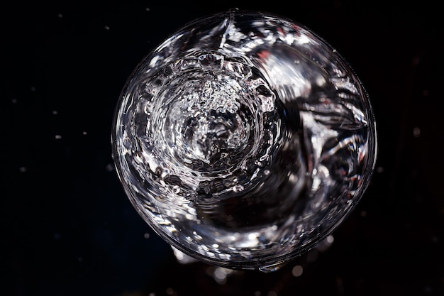 Black background is a glass in which a drop of water falls. splashing water on glass