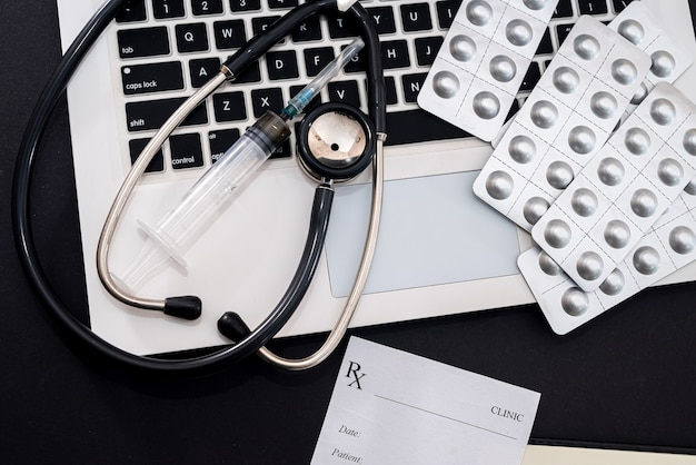 On a black background is a laptop with a stethoscope, pills, syringe, prescription. medicine concept