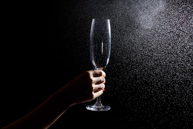 Black background on it is a close-up of a clean glass in his hand. spray on a glass of water. insulated glass