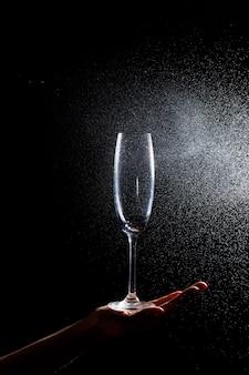 그것에 검은 배경은 그의 손에 깨끗한 유리의 클로즈업입니다. 물 한 잔에 스프레이. 절연 유리