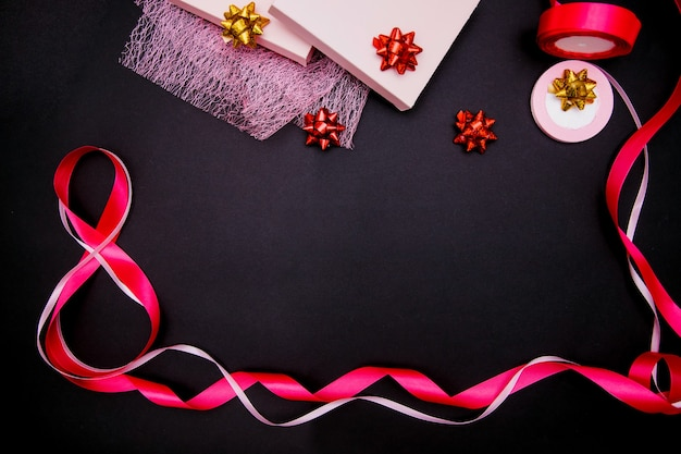 On a black background, a pink satin ribbon in the form of the number eight. gift wrap.