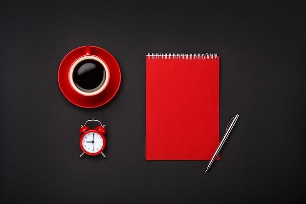 Black background red coffee cup note pad alarm clock blank space desktop