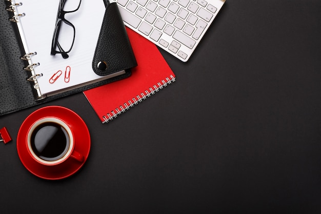 Black background red coffee cup note pad alarm clock flower diary scores keyboard empty space desktop