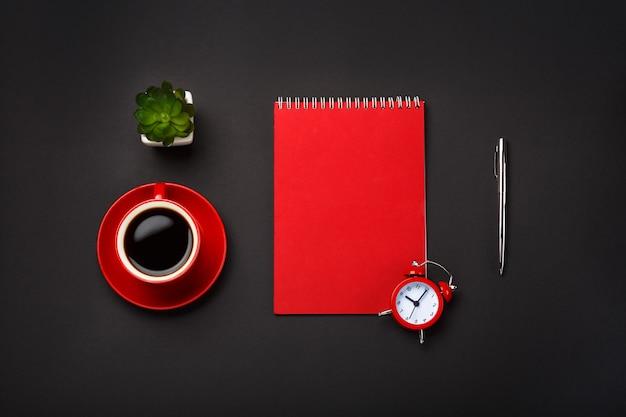 Black background red coffee cup note pad alarm clock flower empty space desktop