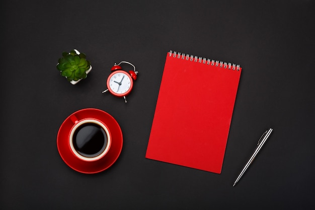 Black background red coffee cup note pad alarm clock flower empty space desktop