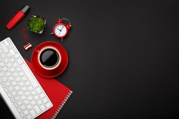 Black background red coffee cup note pad alarm clock flower keyboard blank space desktop
