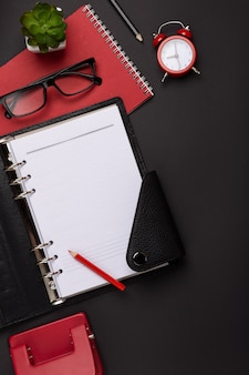 Black background red coffee cup notepad alarm clock flower diary scores keyboard on the table. top view with copy space