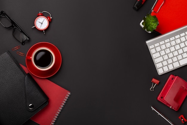Black background red coffee cup notepad alarm clock flower diary scores keyboard on the table