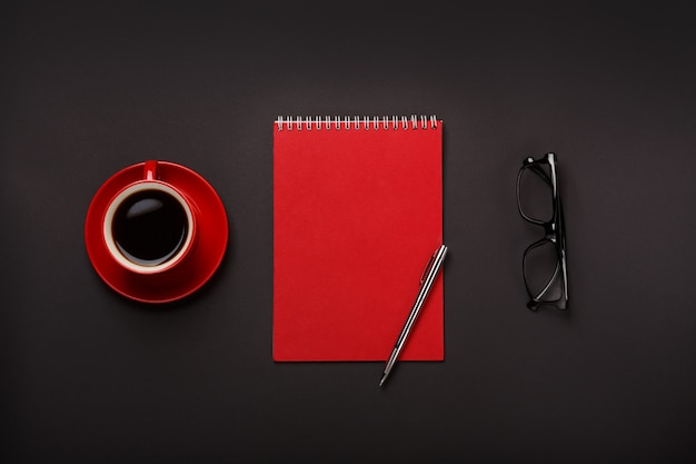 Black background red coffee cup notepad pen glasses empty place desktop.