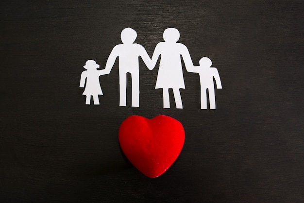 On a black background silhouette of a family and a red heart. world family day.