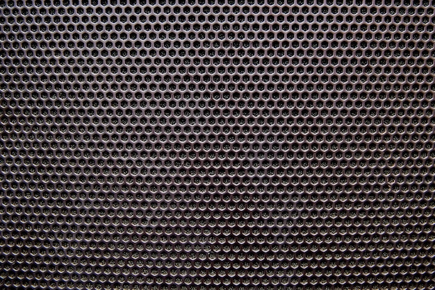 Black background speaker grille close-up.